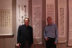Professor John S. C. Wang (left) in front of his calligraphy works